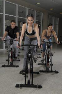 Glada människor på träningscyklar